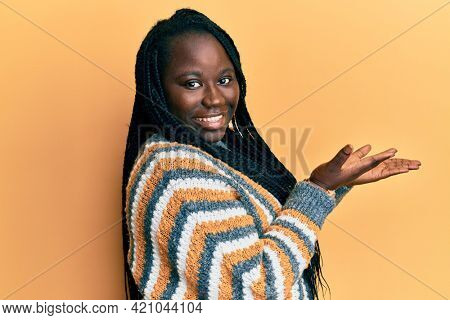 Young black woman with braids wearing casual winter sweater pointing aside with hands open palms showing copy space, presenting advertisement smiling excited happy