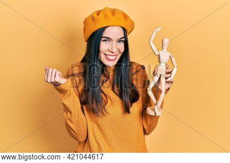 Young brunette woman holding small wooden manikin wearing beret screaming proud, celebrating victory and success very excited with raised arm