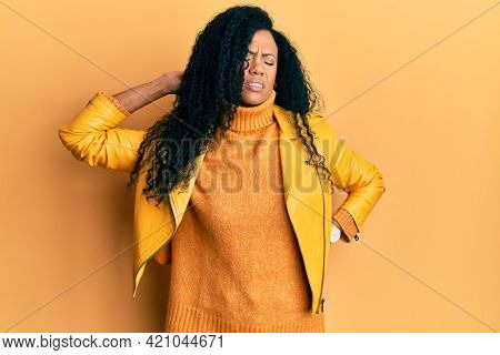Middle age african american woman wearing wool winter sweater and leather jacket suffering of neck ache injury, touching neck with hand, muscular pain