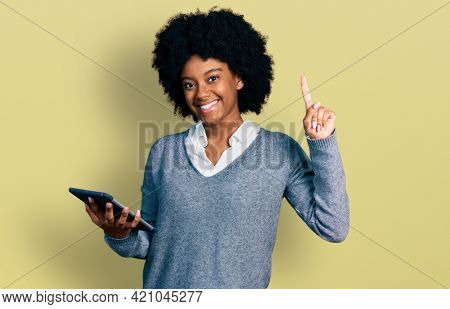 Young african american woman using touchpad device surprised with an idea or question pointing finger with happy face, number one