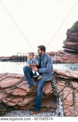 Smiling Dad With A Little Girl In His Arms, Sits On A Rocky Shore Against The Backdrop Of Mountains