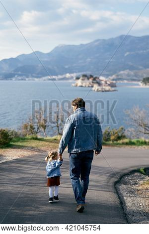 Dad In A Denim Suit Leads A Little Girl In A Dress And A Denim Jacket By The Hand Along An Asphalt R