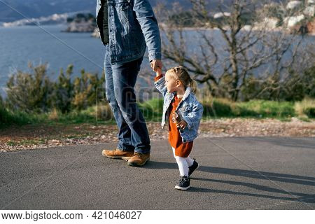 Dad Holds The Hand Of A Little Girl In A Dress And Denim Jacket, Standing On The Road Against The Ba