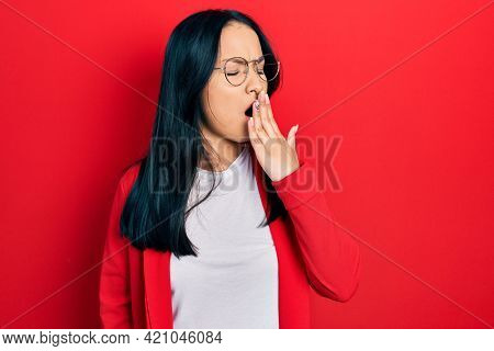Beautiful hispanic woman with nose piercing wearing casual look and glasses bored yawning tired covering mouth with hand. restless and sleepiness.