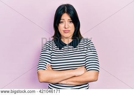 Young hispanic woman with arms crossed gesture skeptic and nervous, frowning upset because of problem. negative person.