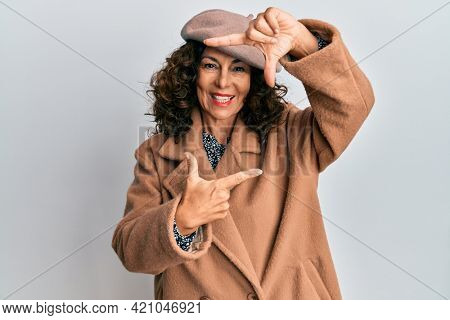 Middle age hispanic woman wearing french look with beret smiling making frame with hands and fingers with happy face. creativity and photography concept.