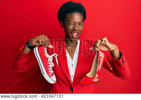 Young african american girl choosing high heel shoes and sneakers winking looking at the camera with sexy expression, cheerful and happy face.