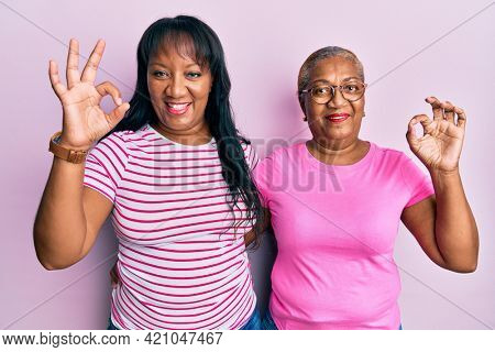 Hispanic family of mother and daughter hugging together with love doing ok sign with fingers, smiling friendly gesturing excellent symbol