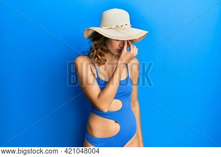 Young caucasian woman wearing bikini and summer hat tired rubbing nose and eyes feeling fatigue and headache. stress and frustration concept.