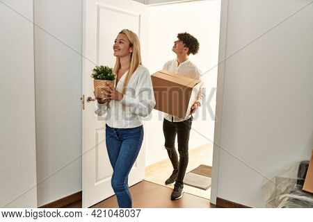Young beautiful couple smiling happy holding cardboard box entering at new home.