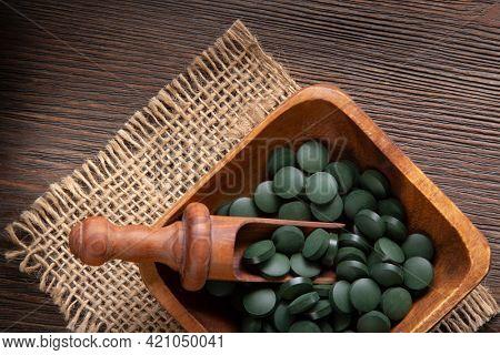 Organic Spirulina Tablets on grey wooden table
