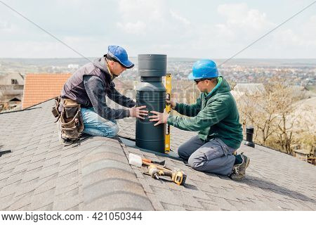 Workers On The Roof Installing Tin Cap On The Iron Chimney. Roofing Construction And Building New Ir