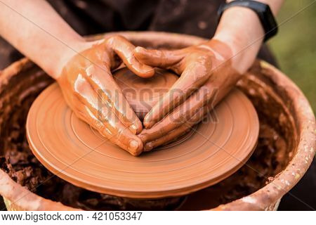 Hands Of Man In Shape Of Heart In Clay On Pottery Wheel Mold Vase. Potter Works In Pottery Workshop