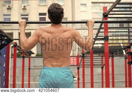 Back View Of Man Doing Pull Up At The Gym. Concept Of Sport. Exercises In Fitness Gym. Male Shirtles