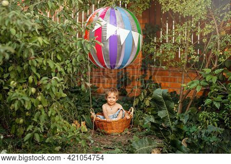 Happy Child With Air Balloon At Sunset In Summer. The Toy Air Balloon For Child. Hot Air Balloon. Cu