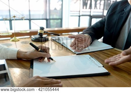 The Lawyer Open Hand Working With The Client To Sign The Contract Provided By The Law Firm.