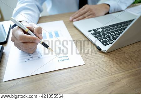 An Executive Or Manager Sitting With A Pen Writing Work On Report Paper On A Desk With A Computer La