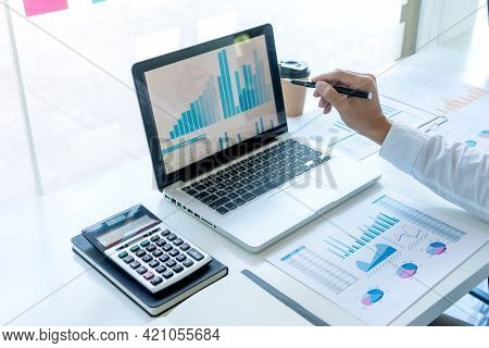 Businessman Pointing At  Graphs Paper Of Business In A Graph Analysis