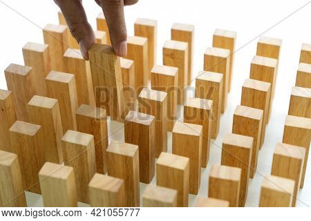Young Man Holds The Wood Block In His Hand To Put It Into The Row
