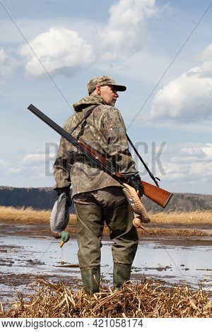 A Duck Hunter With A Duck Decoys In His Hands Stands On The Shallow Water. He's Got A Shotgun On His