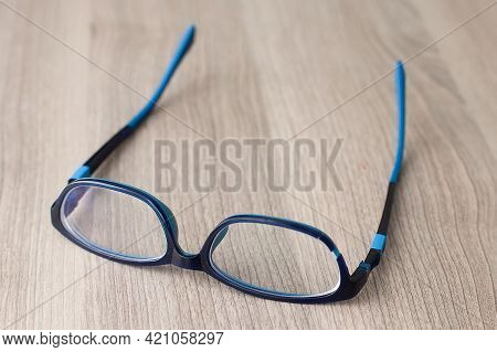 Broken Eyeglasses. Broken Glasses On A Wooden Table. Broken Eyeglass Frames.