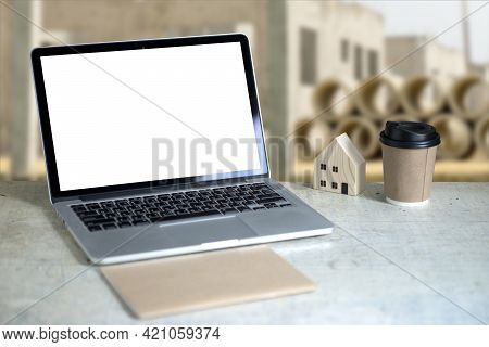 A Computer Notebook On A White Desk With House Model And A Note Have Construction Project Background