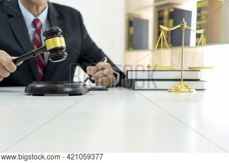 In A Law Firm Judge Or Attorney Holding A Pen And A Gavel