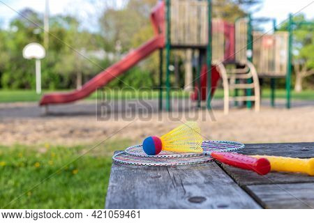 Badminton Game Rackets And Shuttlecock On Wooden Table With Playground In The Park On A Sunny Summer