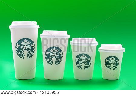 Calgary, Alberta, Canada. May 19, 2021. Starbucks Coffee Cups Of Different Sizes On A Green Backgrou