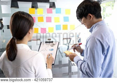 Businessman Uses A Pen In His Hand To Write A Note On A Notepad