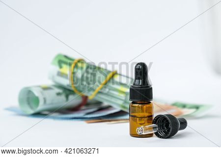 Stack Of Cash Euros And Pipette Medicine. The Concept Of Medical Expensive Medicine, Doctors Salary.