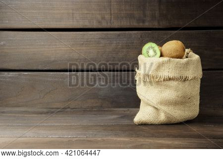 Kiwi On A Wooden Background. Ripe Kiwi In A Sack Bag On A Wooden Background With Copy Space.