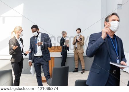 Interracial Business Colleagues In Medical Masks Talking And Pointing With Fingers During Conference