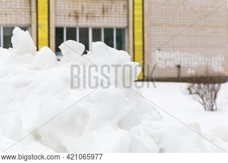 A Large White Snowdrift Piled On A City Street Against The Backdrop Of A House. A Block Of Snow With