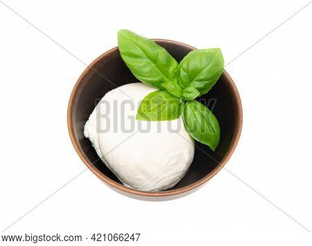 A Ball Of Fresh Mozzarella Ball With Sweet Basil Leaves On Top In A Small Wooden Bowl Isolated On Wh
