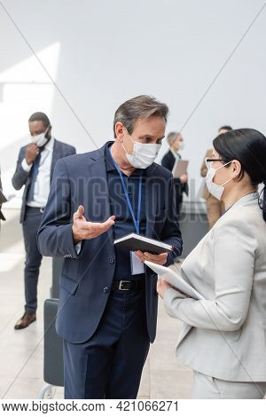 Interracial Business People In Medical Masks, With Notebook And Digital Tablet, Talking In Hall Duri
