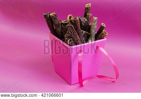 Gift Box Of Pet Treats On A Pink Background. Dried Dog Goodies. Delicious Red Beef Gullet Sticks. Bo
