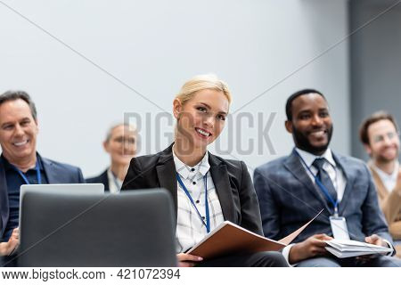 Cheerful Businesswoman With Paper Folder Sitting Near Multiethnic Colleagues During Seminar.