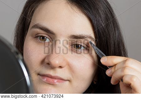 A Brunette Woman Plucked Her Eyebrows In Front Of A Mirror. Correction Of The Shape Of The Eyebrow W