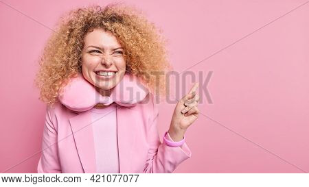 Cheerful Curly Haired Woman With Toothy Smile Points At Upper Right Corner Looks Happily Gives Recom