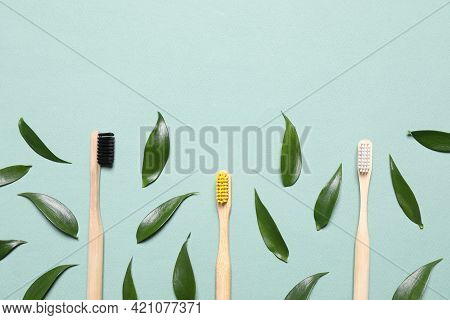Toothbrushes And Fresh Leaves On Pale Turquoise Background, Flat Lay