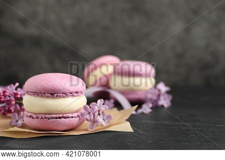 Delicious Violet Macaron And Lilac Flowers On Black Table, Closeup. Space For Text
