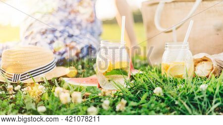 Fresh Homemade Lemonade With Lime And Lemon On The Grass In Sunny Park. Blurred Green Grass And Peop