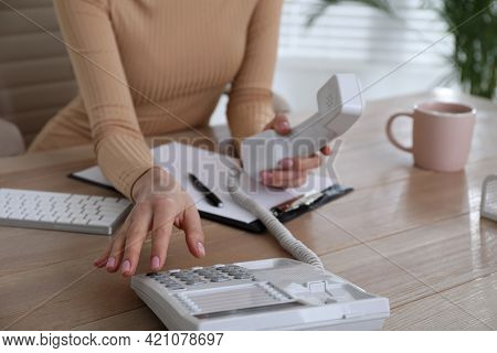 Secretary Dialing Number On Telephone At Wooden Table In Office, Closeup