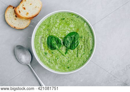 Green Creamy Spinach Soup With Baguette Toasts On A Gray Concrete Background. Healthy Food And Diet.