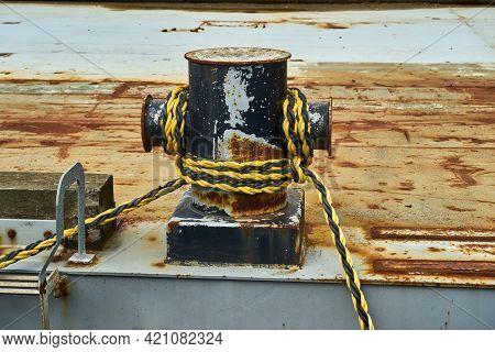 A Cruciform Bollard With Mooring Rope For Securing A Boat. The Cross Shaped Mooring Bitt Has Mooring