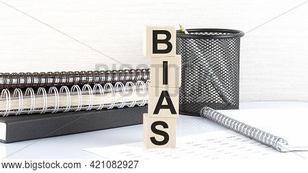 Bias Text On The Wooden Block With Notebooks On White Background