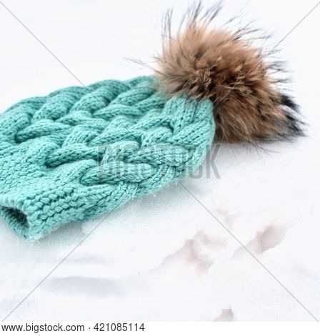 Knitted Turquoise Hat Or Beanie With Pom Pom On A Snow. Winter Apparel Concept. Kids Warm Clothes An