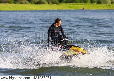 Krasnodar, Russia - July 25, 2020: Young Caucasian Jet Ski Woman Drives Watercraft Making Splashes A