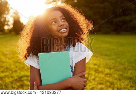 Cheerful African American Schoolgirl Standing With Textbook In Park In Back Lit And Looking Up